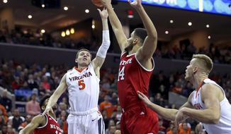 Virginia's Kyle Guy (5) shoots over North Carolina State's Omer Yurtseven (14) in the first half of an NCAA college basketball game Sunday, Jan. 14, 2018, in Charlottesville, Va. (Zack Wajsgras/The Daily Progress via AP)
