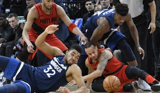 Minnesota Timberwolves' Karl-Anthony Towns, front left, and the Portland Trail Blazers' Damian Lillard, front right, go after the ball during the first half of an NBA basketball game Sunday, Jan. 14, 2018, in Minneapolis. (AP Photo/Tom Olmscheid)