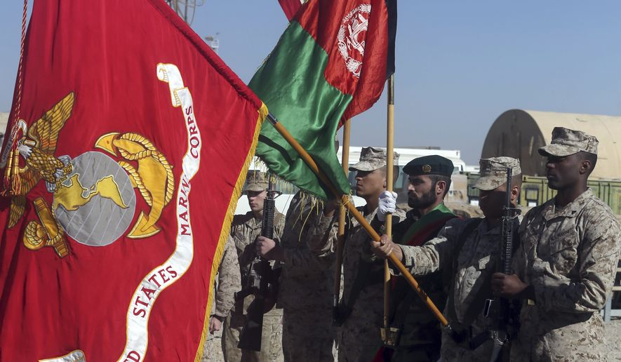 U.S. Marines and an Afghan soldier hold flags during a change of command ceremony at Task Force Southwest atn Shorab military camp of Helmand province, Afghanistan, Monday, Jan. 15, 2018. (AP Photo/Massoud Hossaini)