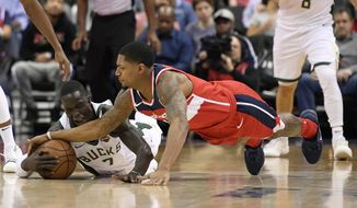 Milwaukee Bucks center Thon Maker (7), of Australia, fights for the ball with Washington Wizards guard Bradley Beal, right, during the first half of an NBA basketball game, Monday, Jan. 15, 2018, in Washington. (AP Photo/Nick Wass)
