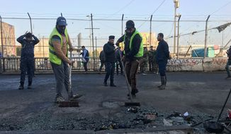 Baghdad municipality workers clean the scene of a double suicide bombing in Baghdad, Iraq, Monday, Jan. 15, 2018. Interior Ministry spokesman said a double suicide bombing in central Baghdad has killed and wounded civilians. (AP Photo/Ali Abdul Hassan)