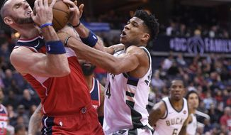 Milwaukee Bucks forward Giannis Antetokounmpo, right, of Greece, battles for the ball against Washington Wizards center Marcin Gortat, left, of Poland, during the first half of an NBA basketball game, Monday, Jan. 15, 2018, in Washington. (AP Photo/Nick Wass)