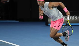Spain's Rafael Nadal dashes to reach the ball as he plays Victor Estrella Burgos of the Dominican Republic during their first round match at the Australian Open tennis championships in Melbourne, Australia, Monday, Jan. 15, 2018. (AP Photo/Vincent Thian)