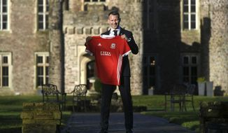New Wales manager Ryan Giggs poses with a Wales shirt after a press conference at Hensol Caste, Vale Resort, Hensol, Wales, Monday, Jan. 15, 2018. Wales has handed Ryan Giggs his first coaching job since ending an illustrious playing career. The Football Association of Wales turned to its former winger, whose only previous experience as a manager was four games in temporary charge of Manchester United in 2014. (Ben Birchal/PA via AP)
