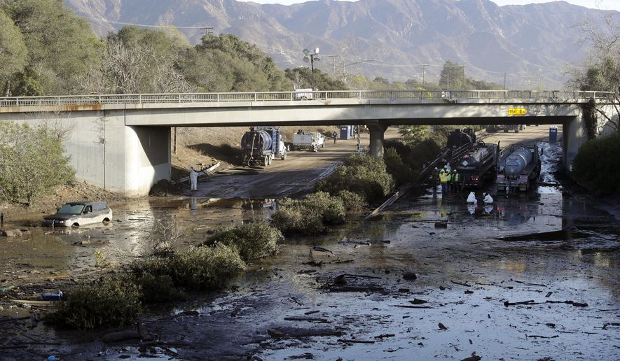 In this Jan. 13, 2018, file photo, crews work on clearing Highway 101 in the aftermath of a mudslide in Montecito, Calif. Officials say the possibility of future catastrophic floods will be in mind as Montecito rebuilds following deadly mudslides that devastated the wealthy coastal hideaway. (AP Photo/Marcio Jose Sanchez, File)