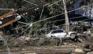 FILE - In this Jan. 10, 2018, file photo, a damaged car sits over fallen and debris behind downed power lines in Montecito, Calif. While an aggressive cleanup could mean Montecito will welcome visitors again in weeks, the rebuilding of infrastructure and hundreds of homes will be measured in months and years. It will also offer a chance to re-imagine aspects of a town that has favored slow growth over the runaway development closer to Los Angeles, 90 miles down the coast. (AP Photo/Marcio Jose Sanchez, File)
