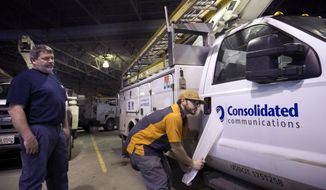 In this Friday, Jan. 12, 2018, photo, Chris Bagley of Sebago Signworks pulls off the covering of a new Consolidated Communications logo he applied to the door of a former FairPoint truck as fleet mechanic Steve Morin looks on in Portland, Maine. Consolidated Communications bought FairPoint Communications and is discarding the old name and making plans to upgrade service of tens of thousands of customers in northern New England. (AP Photo/Robert F. Bukaty)