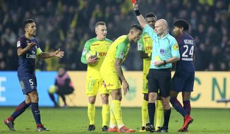Referee Tony Chapron gives a red card to Nantes defender Diego Carlos, left, after Carlos inadvertently clipped the referee's heels during the French League One soccer match between Nantes and Paris Saint Germain, in Nantes, western France, Sunday, Jan. 14, 2018. French official Tony Chapron kicked out in retribution at Nantes defender Diego Carlos during a league game on Sunday, and then promptly showed Carlos a red card. (AP Photo/David Vincent)