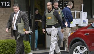 FILE - In this April 21, 2017 file photo, FBI agents leave the office of Dr. Fakhruddin Attar at the Burhani Clinic in Livonia, Mich., after completing a search for documents. A federal judge in Detroit has dismissed one charge against Attar and Dr. Jumana Nagarwala in connection with a female genital mutilation case.  U.S. District Judge Bernard Friedman ruled Sunday, Jan. 14, 2018, that the doctors didn't commit conspiracy to transport a minor with intent to engage in criminal sexual activity.   (Clarence Tabb Jr. /Detroit News via AP, File)