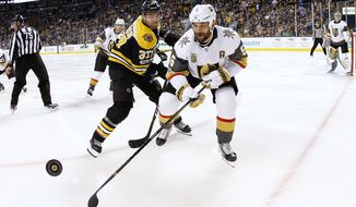 FILE - In this Nov. 2, 2017, file photo, Vegas Golden Knights' Deryk Engelland (5) and Boston Bruins' Patrice Bergeron watch the puck during the second period an NHL hockey game in Boston. The Knights have signed Engelland to a $1.5 million, one-year contract extension. (AP Photo/Winslow Townson, File)