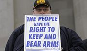 """In this Jan. 12, 2018 photo, John Doll, of Renton, Wash., holds a sign that reads """"The people have the right to keep and bear arms"""" during a gun rights rally at the Capitol in Olympia, Wash. A Washington state Legislature Senate committee held a public hearing Monday, Jan. 15, on several bills related to guns, including measures to prohibit high-capacity magazines and to ban so-called bump stocks, trigger modification devices designed to increase the rate of fire of a firearm. (AP Photo/Ted S. Warren)"""