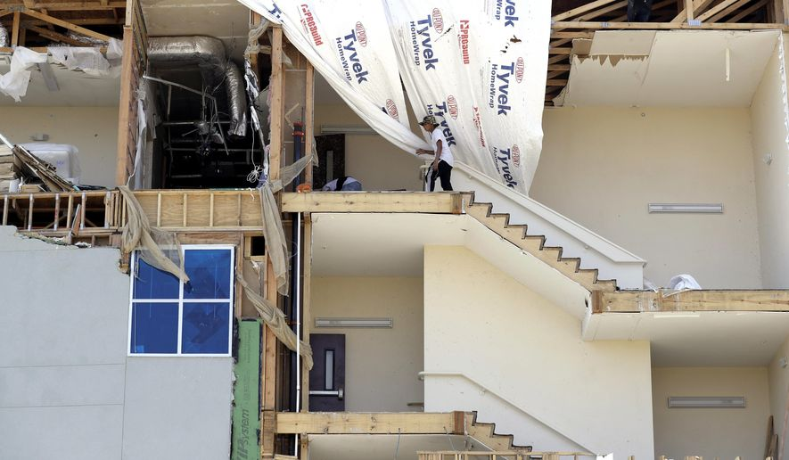FILE - In this Sept. 2, 2017, file photo, workers pick up debris in a staircase of a four-story hotel exposed when the wall fell during Hurricane Harvey, in Rockport, Texas. Texas coastal towns where Hurricane Harvey made landfall are working to restore tourism and other economic attractions nearly five months after the storm. (AP Photo/Eric Gay, File)