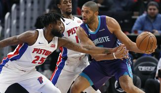 Detroit Pistons forward Reggie Bullock (25) fouls Charlotte Hornets guard Nicolas Batum (5) as Pistons guard Ish Smith, center, helps defend the basket during the first half of an NBA basketball game Monday, Jan. 15, 2018, in Detroit. (AP Photo/Duane Burleson)