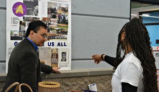 In a photo provided by the Cherokee Nation,  Cherokee Nation Secretary of State Chuck Hoskin Jr., left, looks over an exhibit about the Cherokee Freeman during a visit to the Martin Luther King Center in Muskogee, Okla., on Monday, Jan. 15, 2018. Leaders of the Cherokee Nation marked Martin Luther King Jr. Day by welcoming the descendants of slaves into their tribe after years of exclusion. (Courtesy of the Cherokee Nation via AP)