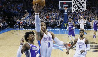 Oklahoma City Thunder guard Russell Westbrook (0) shoots in front of Sacramento Kings guard De'Aaron Fox (5) and teammate Paul George (13) in the second quarter of an NBA basketball game in Oklahoma City, Monday, Jan. 15, 2018. (AP Photo/Sue Ogrocki)