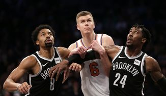 Brooklyn Nets' Spencer Dinwiddie, left, Rondae Hollis-Jefferson, right, and New York Knicks' Kristaps Porzingis look for a rebound during the first half of the NBA basketball game at the Barclays Center, Monday, Jan. 15, 2018 in New York. (AP Photo/Seth Wenig)