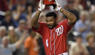 FILE - In this Aug. 13, 2017 file photo, Washington Nationals' Howie Kendrick throws off his batting helmet as he celebrates his walkoff grand slam in the 11th inning of the second baseball game of a doubleheader against the San Francisco Giants in Washington.  The Nationals have agreed to terms on a $7 million, two-year contract with veteran outfielder Howie Kendrick.  (AP Photo/Nick Wass)
