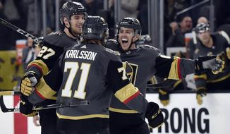 Vegas Golden Knights' Shea Theodore (27), William Karlsson (71) and Jonathan Marchessault celebrate Karlsson's goal against the Edmonton Oilers during the second period of an NHL hockey game Saturday, Jan. 13, 2018, in Las Vegas. (AP Photo/David Becker)