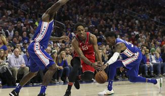 Toronto Raptors guard DeMar DeRozan (10) attempts to dribble between Philadelphia 76ers forwards Amir Johnson, left, and Robert Covington, right during the second half of an NBA basketball game in Philadelphia, Monday, Jan. 15, 2018. (AP Photo/Rich Schultz)