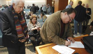 New Mexico state Sen. Richard Martinez, D-Epanola, right, and Rep. Nick Salazar, D-Ohkay Owingeh, left, sign paperwork showing they attended a mandatory anti-harassment training session at the state Capitol in Santa Fe, N.M. Monday, Jan. 15, 2018. The training is part of an effort to make the Capitol work environment safer amid a nationwide debate over sexual misconduct. (AP Photo/Morgan Lee)