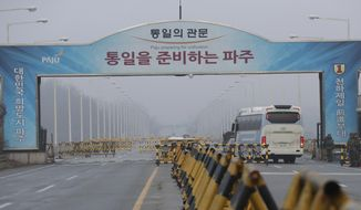 A bus carrying the South Korean delegations passes as South Korean soldier salutes at Unification Bridge, which leads to the Panmunjom in the Demilitarized Zone in Paju, South Korea, Monday, Jan. 15, 2018.  The rival Koreas agreed to discuss a North Korean art troupe's visit to the Pyeongchang Winter Olympics in the South. (AP Photo/Lee Jin-man)