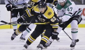 Boston Bruins left wing Brad Marchand (63) and Dallas Stars right wing Alexander Radulov (47), of Russia, vie for control of the puck during the first period of an NHL hockey game, Monday, Jan. 15, 2018, Boston. (AP Photo/Steven Senne)