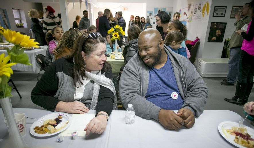 Eileen Walter and Anthony Carr visit at the 10th annual MLK Peace through P.I.E. Social at Sweet Home Missionary Baptist Church in Austin, Texas, on Saturday Jan. 13, 2018. About 250 people came together for the pie social to celebrate Martin Luther King's message of peace and unity. The event also included a silent pie auction to support renovations of the historic church in the Clarksville neighborhood. Peace through P.I.E., which stands for Peace Includes Everyone, was started in Austin by Luanne Stovall, who wanted to create a food tradition to bring people together for the MLK holiday. (Jay Janner/Austin American-Statesman via AP)