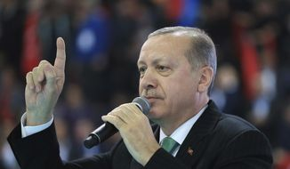 "Turkey's President Recep Tayyip Erdogan talks to supporters of his ruling Justice and Development Party (AKP), at a rally in Yozgat, eastern Turkey, Sunday, Jan. 14, 2018. Erdogan said Sunday the country will launch a military assault on a Kurdish enclave in northern Syria ""in the coming days,"" and urged the U.S. to support its efforts. (Pool Photo via AP)"