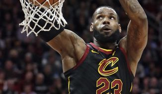 Cleveland Cavaliers' LeBron James dunks against the Golden State Warriors in the first half of an NBA basketball game, Monday, Jan. 15, 2018, in Cleveland. (AP Photo/Tony Dejak)