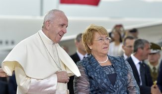 In this picture made available Tuesday, Jan. 16, 2018, Pope Francis is welcomed by Chile's President Michelle Bachelet, right, upon his arrival at the international airport in Santiago, Chile, Monday, Jan. 15, 2018. (L'Osservatore Romano/Pool Photo via AP)