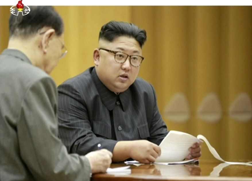 FILE - In this file image made from undated video of a news bulletin aired by North Korea's KRT on Sept. 3, 2017, North Korea's leader Kim Jong Un holds the Presidium of the Political Bureau of the Central Committee. Japan's public broadcaster mistakenly sent an alert warning citizens of a North Korean missile launch and urging them to seek immediate shelter, then retracted it minutes later, days after a similar error in Hawaii. NHK television issued the message Tuesday, Jan. 16, 2018 on its internet and mobile news sites as well as on Twitter, saying North Korea appeared to have fired a missile at Japan. NHK deleted its tweet after several minutes, issued a correction and apologized several times on air. (KRT via AP Video, file)