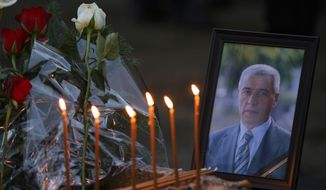 Flowers, candles and a picture of Kosovo Serb politician Oliver Ivanovic, who was shot dead Tuesday morning by still-unknown assailants,  at the scene of the shooting in front of his office in the northern, Serb-dominated part of Mitrovica, Kosovo, Tuesday, Jan. 16, 2018. People from Kosovo's Serb minority say they are in shock over the killing of a moderate politician who was gunned down in an attack in a northern town. (AP Photo/Bojan Slavkovic)