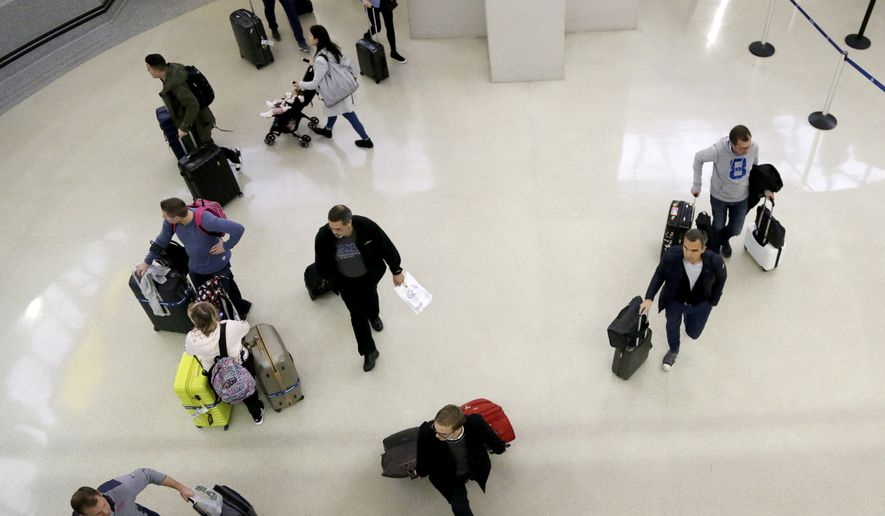In this Oct. 26, 2017, file photo, passengers leave the customs and immigration area with their luggage at the international arrivals terminal at Newark Liberty International Airport in Newark, N.J. (AP Photo/Julio Cortez, File)