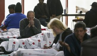 Jeremy Roberts sits on a cot at a warming shelter opened by the Harris County Precinct One Constables Office and the American Red Cross at Pleasant Grove Missionary Baptist Church as freezing weather moves through the region Tuesday, Jan. 16, 2018, in Houston. (Michael Ciaglo/Houston Chronicle via AP)