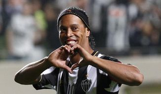 FILE - In this July 11, 2013 file photo, Brazil's Atletico Mineiro's Ronaldinho celebrates his team's victory over Argentina's Newell's Old Boys at the end of a Copa Libertadores semifinal soccer match in Belo Horizonte, Brazil. The brother and agent of 2005 Ballon d'Or winner Ronaldinho says the former Brazil and Barcelona playmaker has retired from football. (AP Photo/Bruno Magalhaes, File) **FILE**