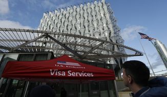 A Visa Services gazebo stands outside as the first group of Visa applicants to go into the new United States Embassy building in London, wait in line outside, Tuesday, Jan. 16, 2018. The new U.S. Embassy in London, denigrated last week by President Donald Trump as too expensive and in a poor location, is set to open to the public. The embassy, in the formerly industrial Nine Elms neighborhood, will open for public business Tuesday. (AP Photo/Matt Dunham)