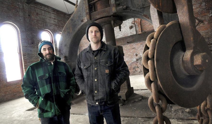 In this Jan. 5, 2018, photo, Patrick Quinn, left, head blacksmith and forging program coordinator, and Dan Neville, jeweler and metal smithing studio coordinator, plan to open a school in the old Bethelem Steel blacksmith shop on Iron Street in downtown Johnstown. (Thomas Slusser/The Tribune-Democrat via AP)