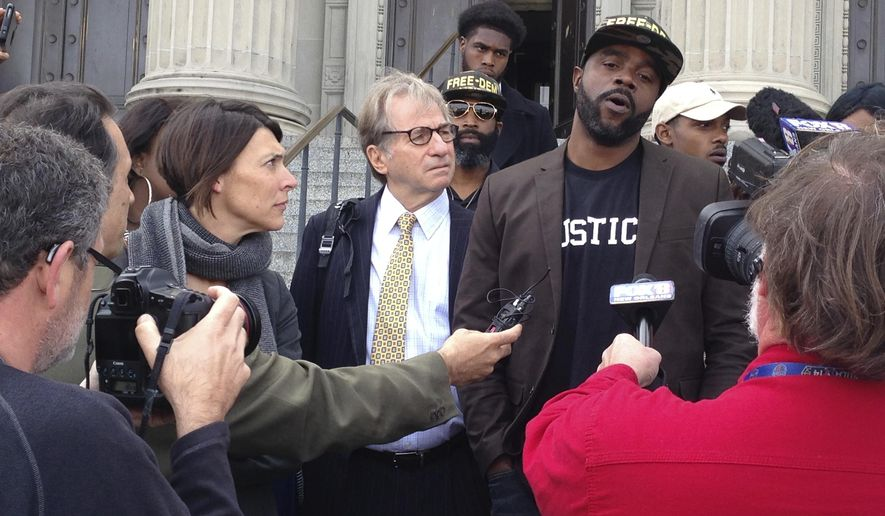 FILE - In this Jan. 26, 2017, file photo, Robert Jones, right, speaks with reporters, with defense attorneys Emily Maw, left, and Barry Scheck, at the New Orleans courthouse. Almost a year after charges against him were formally dropped in a 1992 crime spree, Jones, a man who spent more than 20 years behind bars, is seeking damages from the New Orleans district attorney's office. Attorneys for Jones filed the federal lawsuit Tuesday, Jan. 16, 2018. (AP Photo/Kevin McGill, File)