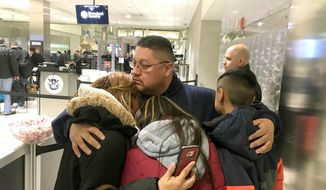 In this Monday, Jan. 15, 2018 photo, Jorge Garcia hugs his wife, Cindy Garcia, and their two children at Detroit Metro Airport moments before boarding a flight to Mexico. Garcia, who had lived in the U.S. for nearly 30 years, was deported to Mexico.  (Niraj Warikoo /Detroit Free Press via AP)