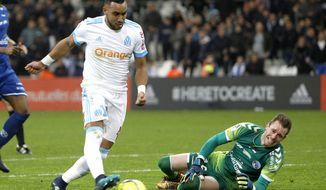 Marseille's Dimitri Payet, left, controls the ball past Strasbourg's Alexandre Oukidja, to score during the League One soccer match between Marseille and Strasbourg, at the Velodrome stadium, in Marseille, southern France, Tuesday, Jan.16, 2018. (AP Photo/Claude Paris)