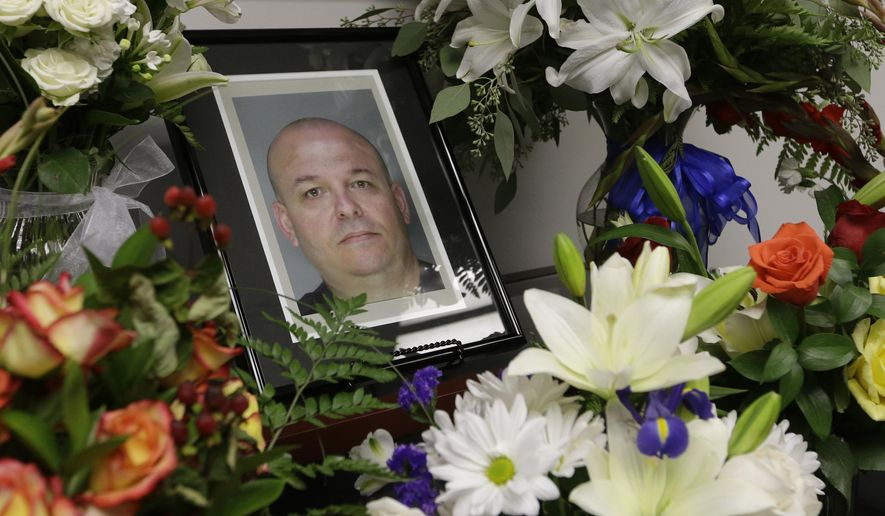"In this Oct, 28, 2014, file photo, flowers surround a photo of slain Sacramento County Deputy Sheriff Daniel Oliver at the Sacramento County Sheriff's office in Sacramento, Calif. Luis Enrique Monroy Bracamontes, the suspect being tried in the slayings of  Oliver and Scott Brown, called Brown a ""coward"" as his murder trial began on Tuesday, Jan. 16, 2018. (AP Photo/Rich Pedroncelli, File)"