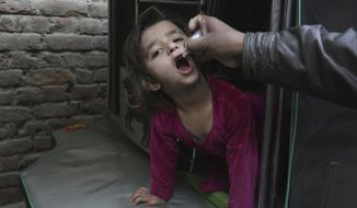 A health worker gives a polio vaccine to a child in Lahore, Pakistan, Tuesday, Jan. 16, 2018. Pakistani authorities launched an anti-polio campaign in Punjab province as polio remains endemic in Pakistan. (AP Photo/K.M. Chaudary)