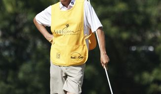 "While leaning on the pin flag, Jim ""Bones"" Mackay stands on the seventh green during the third round of the Sony Open golf tournament, Saturday Jan. 13, 2018, in Honolulu. Although he retired last year, MacKay is filling in for Justin Thomas' injured caddie. (AP Photo/Marco Garcia)"