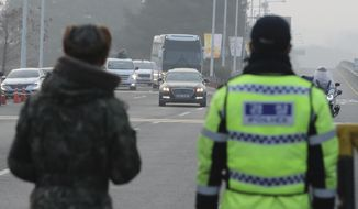 A South Korean soldier, left, and a police officer stand as vehicles carrying the South Korean delegation pass near Unification Bridge, which leads to the Panmunjom in the Demilitarized Zone in Paju, South Korea, Wednesday, Jan. 17, 2018. South Korean delegation departed for Panmunjom on Wednesday morning for talks with North Korea to further discuss the North's paricipation in the upcoming Winter Olympics. (AP Photo/Lee Jin-man)