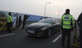South Korean police officers stand as vehicles carrying the South Korean delegation pass at the check point at Unification Bridge, which leads to the Panmunjom in the Demilitarized Zone in Paju, South Korea, Wednesday, Jan. 17, 2018. South Korean delegation departed for Panmunjom on Wednesday morning for talks with North Korea to further discuss the North's paricipation in the upcoming Winter Olympics. (AP Photo/Lee Jin-man)