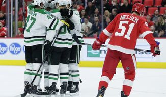 Dallas Stars center Jason Spezza, second from left, celebrates his goal with teammates, including Dallas Stars right wing Alexander Radulov (47), of Russia, as Detroit Red Wings center Frans Nielsen (51), of Denmark, skates off during the first period of an NHL hockey game Tuesday, Jan. 16, 2018, in Detroit. (AP Photo/Duane Burleson)