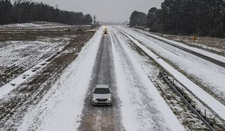 Traffic makes its way north on Highway 7 as snow falls in Oxford, Miss., on Tuesday, Jan. 16, 2018. The National Weather Service on Tuesday issued winter storm warnings in parts of Louisiana and Mississippi. (Bruce Newman/The Oxford Eagle via AP)