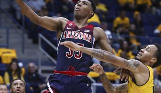 Arizona's Allonzo Trier, left, lays up a shot past California's Don Coleman in the second half of an NCAA college basketball game Wednesday, Jan. 17, 2018, in Berkeley, Calif. (AP Photo/Ben Margot)