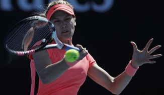 Canada's Eugenie Bouchard makes a forehand return to France's Oceane Dodin during their first round match at the Australian Open tennis championships in Melbourne, Australia, Tuesday, Jan. 16, 2018. (AP Photo/Vincent Thian)