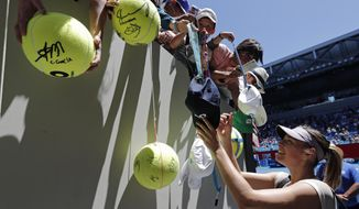 Russia's Maria Sharapova signs autographs after defeating Germany's Tatjana Maria during their first round match at the Australian Open tennis championships in Melbourne, Australia, Tuesday, Jan. 16, 2018. (AP Photo/Vincent Thian)